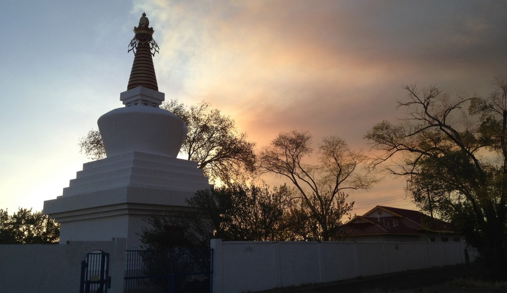 At Kagyu Shenpen Kunchab stupa in Santa Fe the day before the pilgrimage begins, wildfires produce smoke over the mountains
