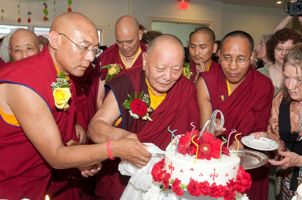 Khenpo Karthar Rinpoche cutting the birthday cake at his 90th birthday party with Lodroe Nyima Rinpoche on his right. (photo by Stephanie Colvey)