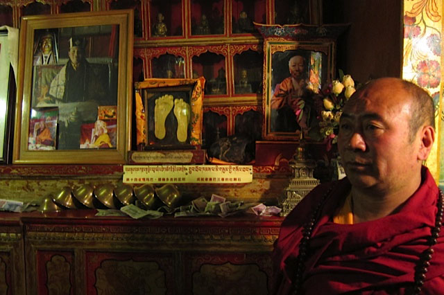 lucicblogAttendent Lama in Karmapa's audience hall, with footprints of the 14th Karmapa