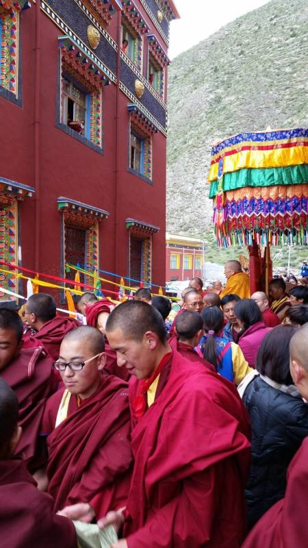 Thrangu Rinpoche can be seen sitting under the parasol. He was tossing out blessing rice to the masses that were passing beneath him and the other lamas.